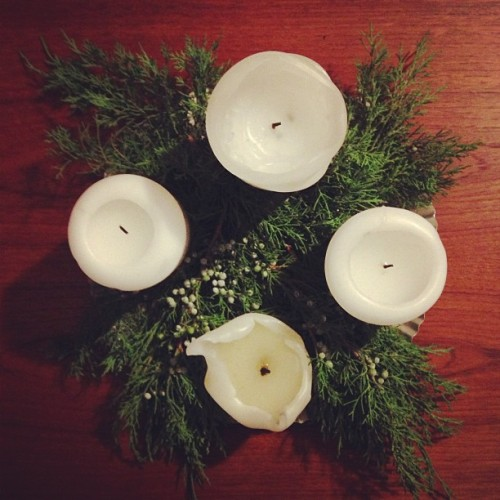 Juniper branches and berries surrounding four candles