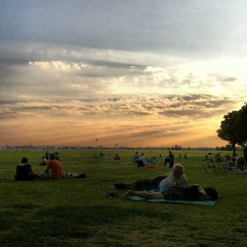 People resting on the lawn at sunset at Tempelhofer Feld