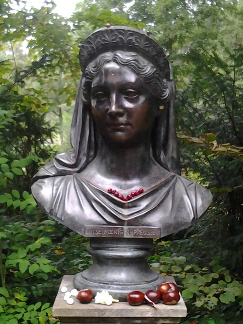 Outdoor bronze bust of Queen Luise decorated with berries and seeds.